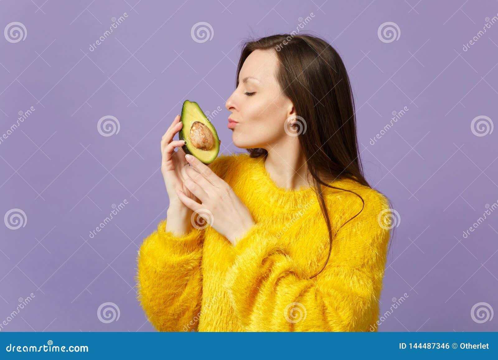 A jovem mulher bonito na camiseta da pele que mantém os olhos fechou guardar, beijando a metade do abacate maduro fresco isolado