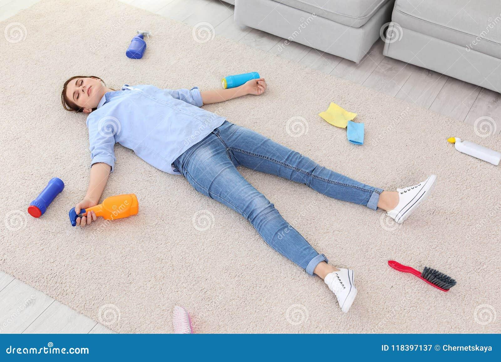 Jovem mulher cansado que encontra-se no tapete cercado por fontes de limpeza