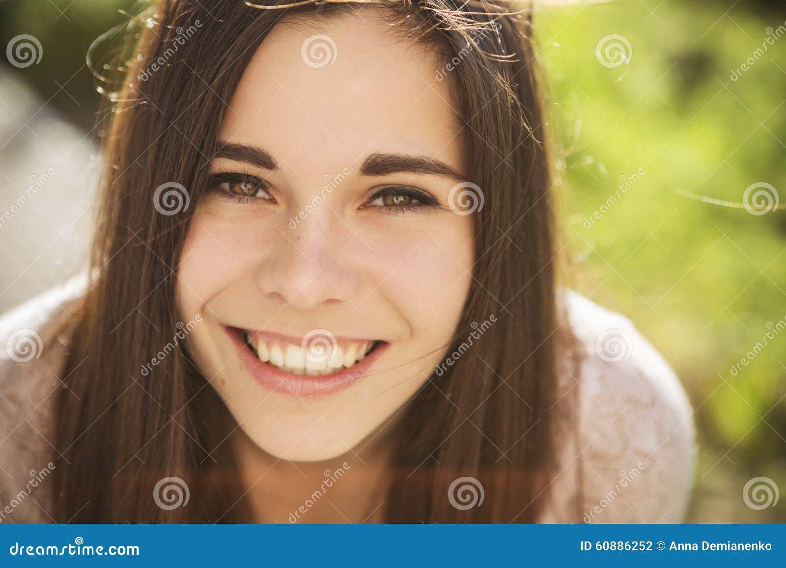 Jovem mulher caucasiano moreno bonita que laughting mostrando o perfe