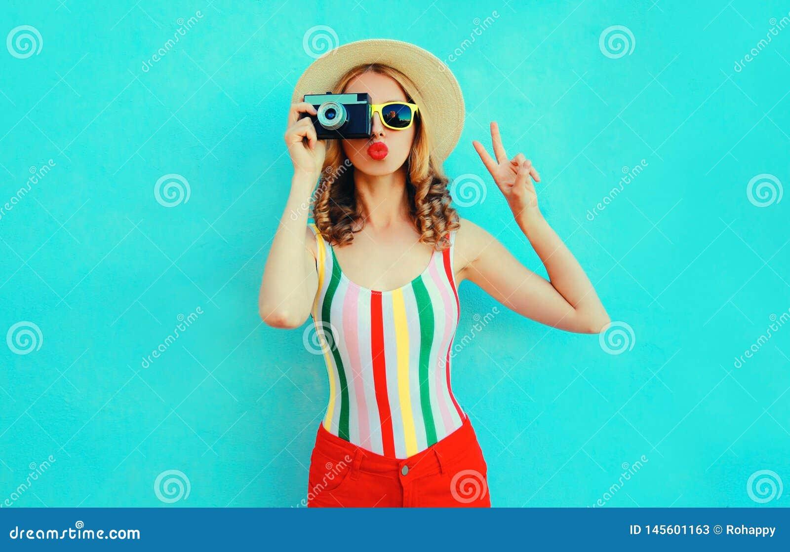 A jovem mulher colorida que guarda a c?mera retro, os bordos vermelhos de sopro envia o beijo do ar no chap?u de palha do ver?o q