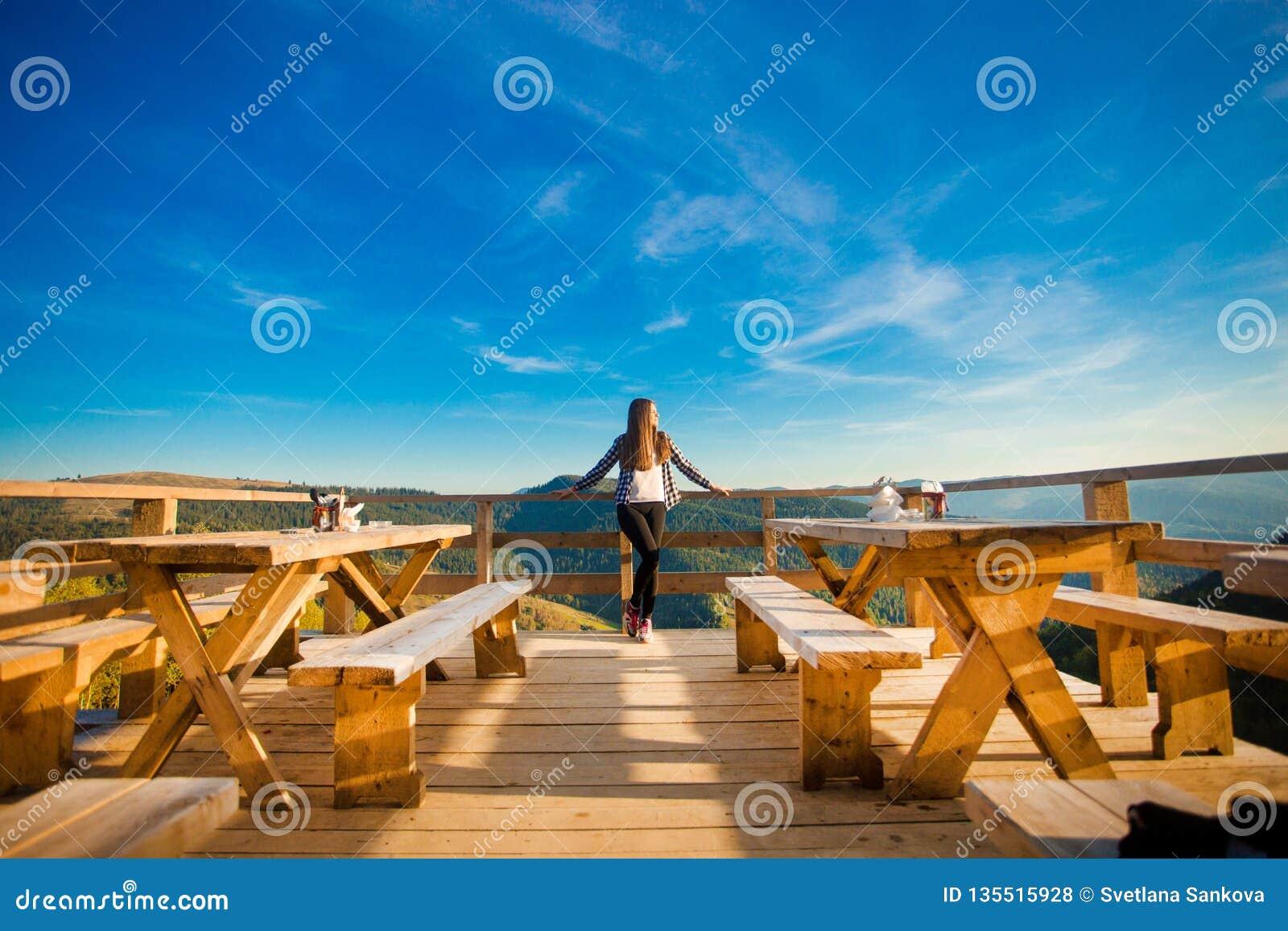 A jovem mulher com cabelo longo tem o resto no café do ar livre sobre montanhas e aprecia a vista