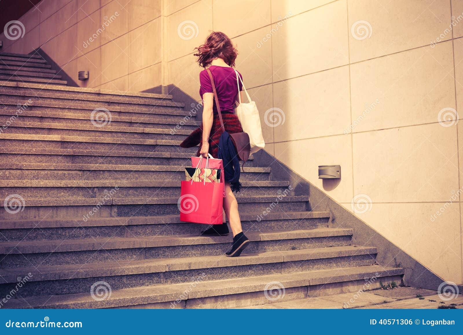 Jovem mulher com compra que anda acima das escadas
