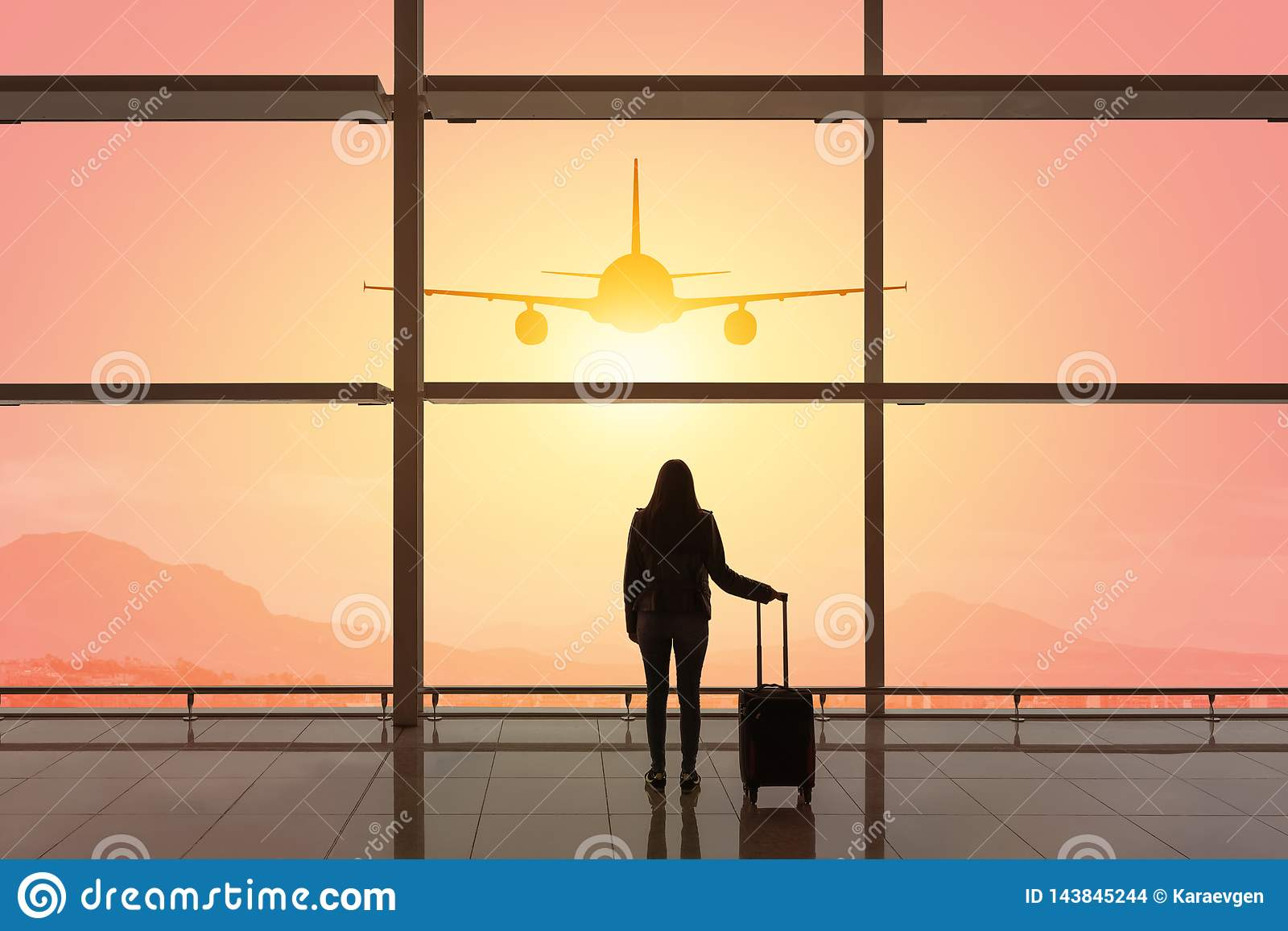 Jovem mulher com a mala de viagem no sal?o da partida no aeroporto conceito do curso