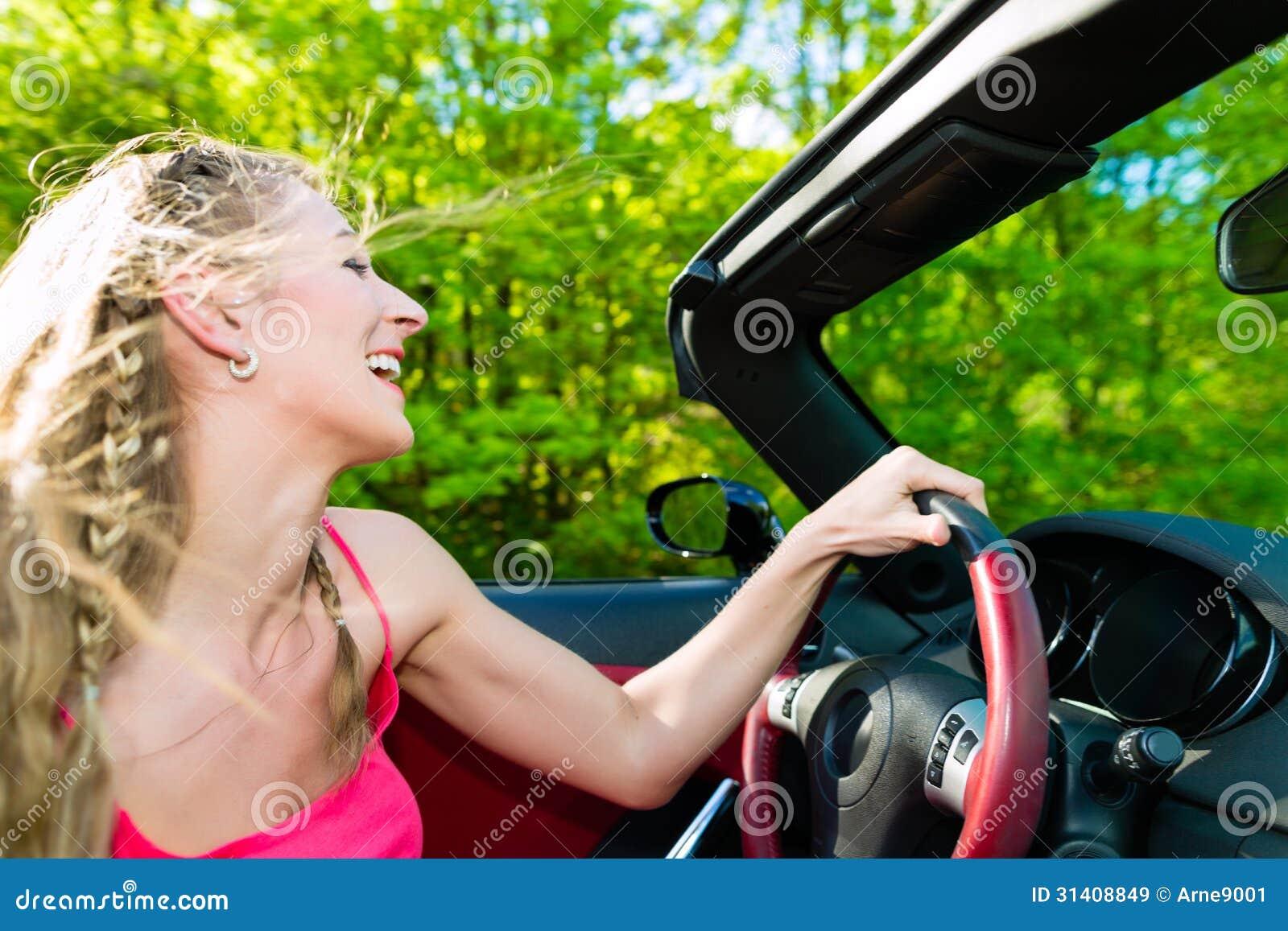 Jovem mulher com o cabriolet no verão na viagem do dia