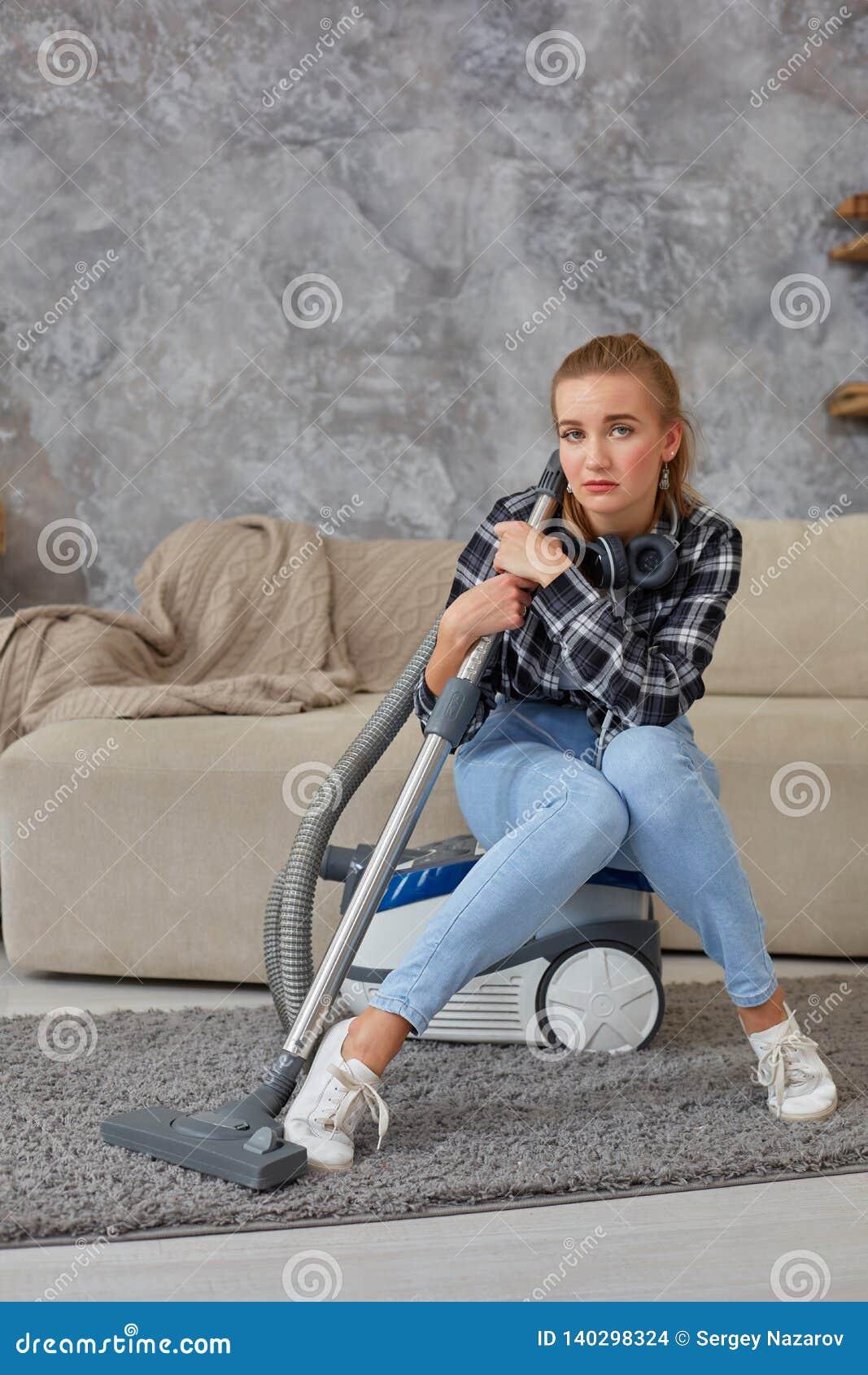 Jovem mulher com o equipamento da limpeza pronto para limpar a casa, assento no sofá fatiga