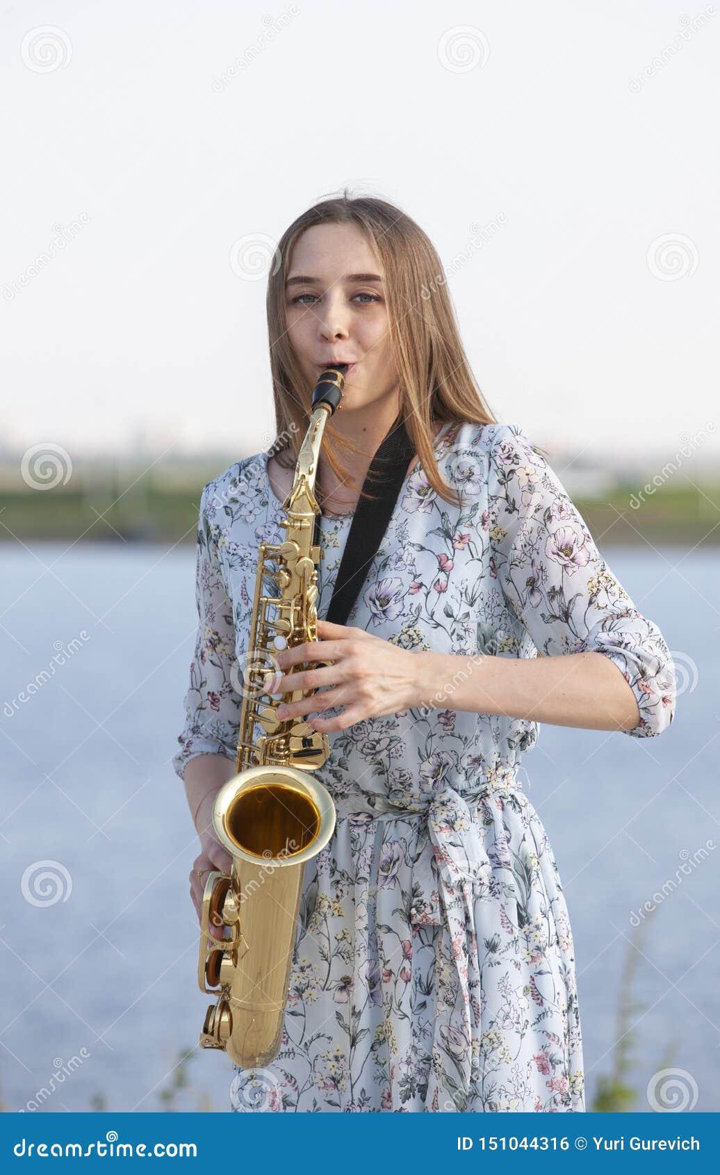 Jovem mulher com o saxofone no parque