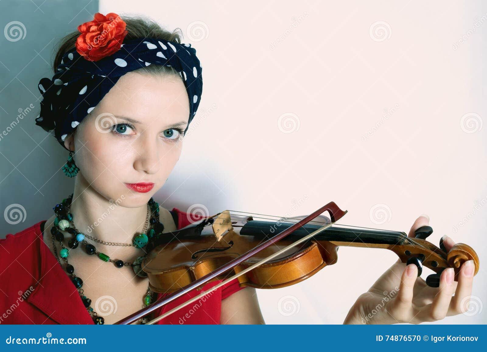 Jovem mulher com o violino no fundo claro