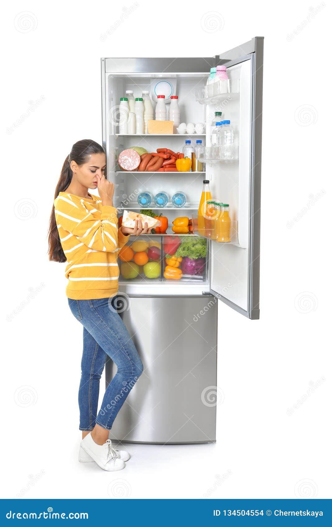 Jovem mulher com queijo expirado perto do refrigerador aberto