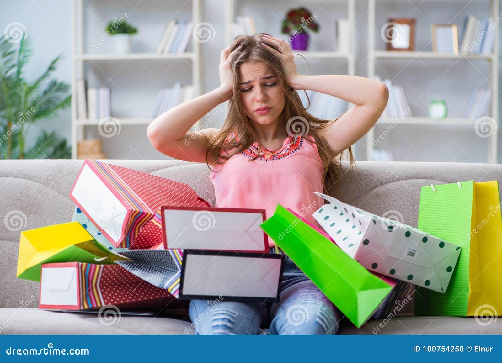 A jovem mulher com sacos de compras dentro dirige no sofá