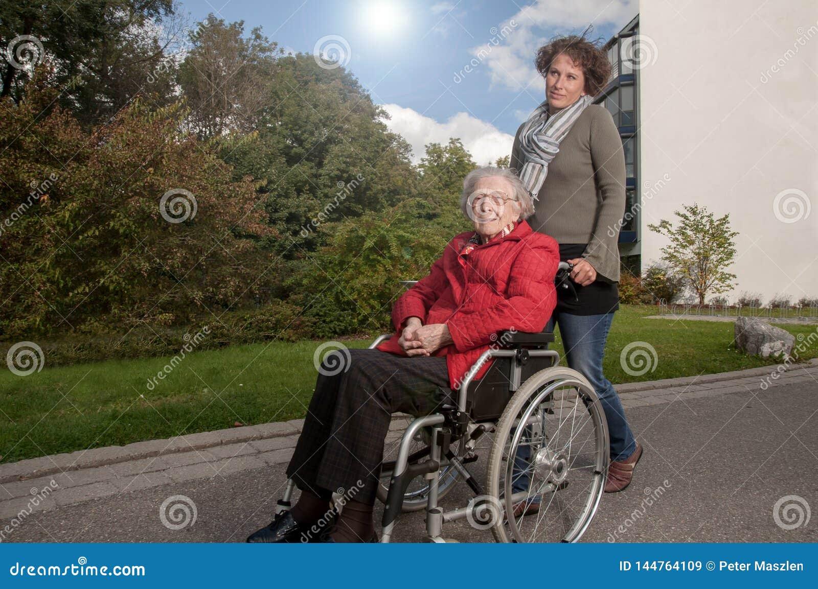 Jovem mulher com a mulher superior que senta-se na cadeira de rodas
