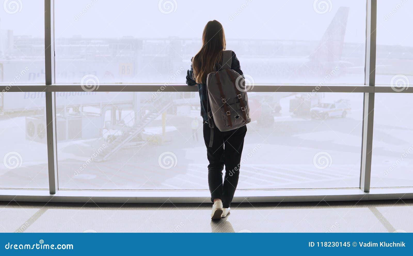 Jovem mulher com a trouxa perto da janela terminal Turista fêmea caucasiano que usa o smartphone na sala de estar do aeroporto Cu