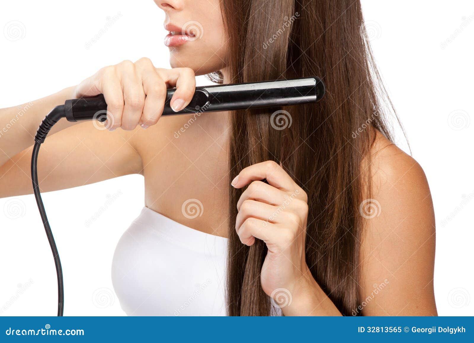 Jovem mulher com um straightener do cabelo