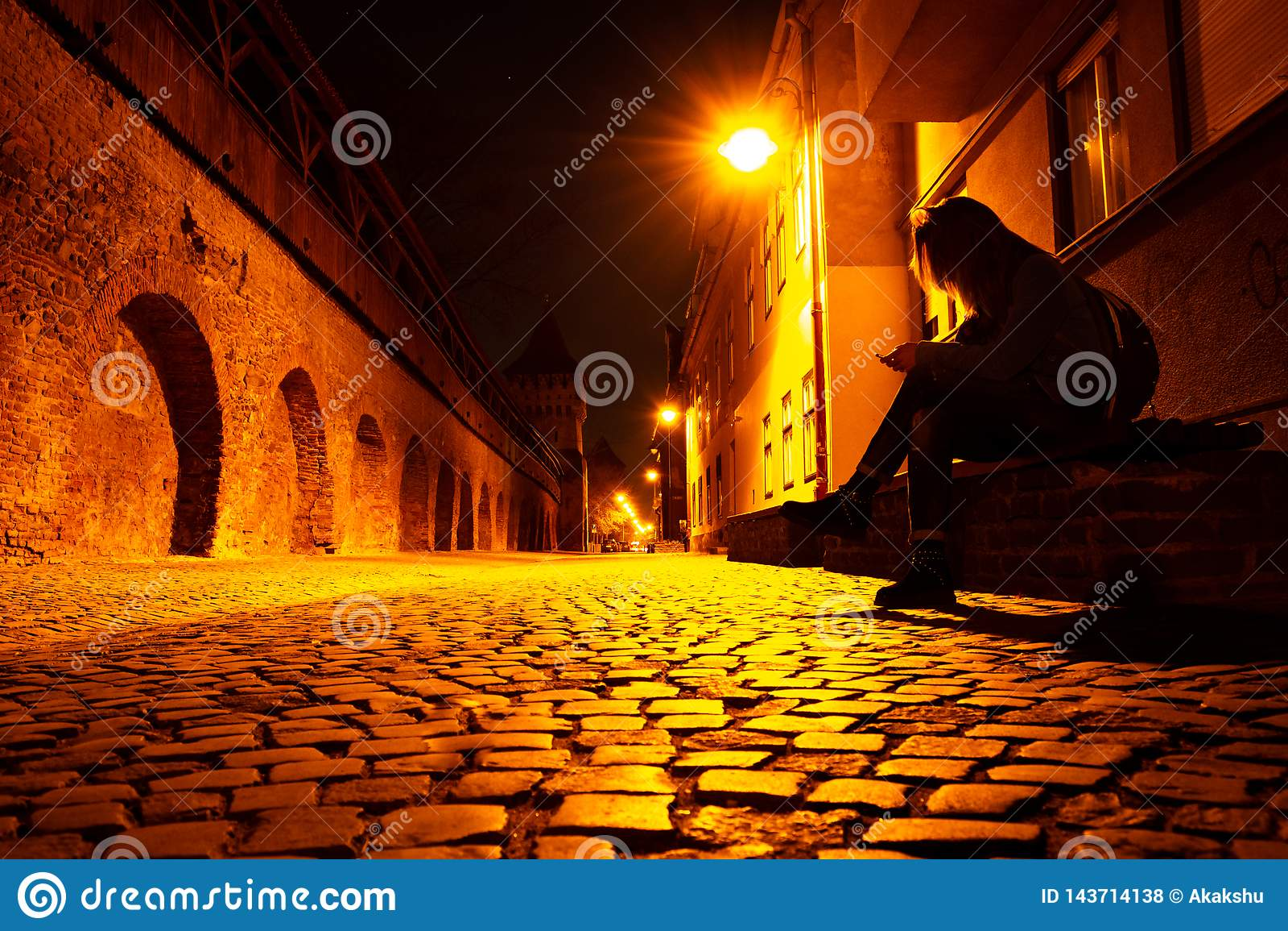 Jovem mulher com um telefone à disposição, em um banco, tarde na noite, em uma rua de pedrinha medieval do estilo em Sibiu, Romên