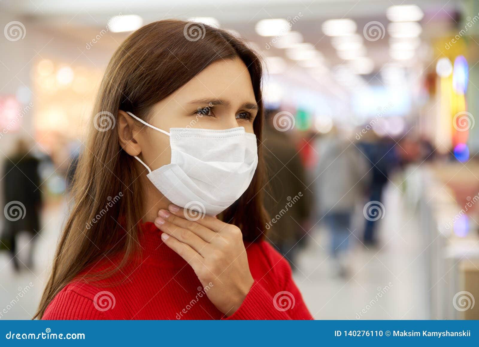 A jovem mulher com uma cara olhando de sobrancelhas franzidas guarda sua garganta e veste uma máscara protetora ao comprar na ala