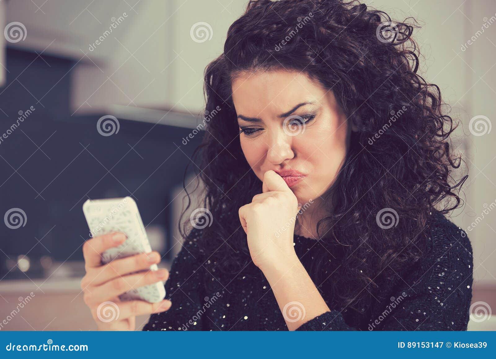 Jovem mulher confusa virada que olha a mensagem de texto da leitura do telefone celular