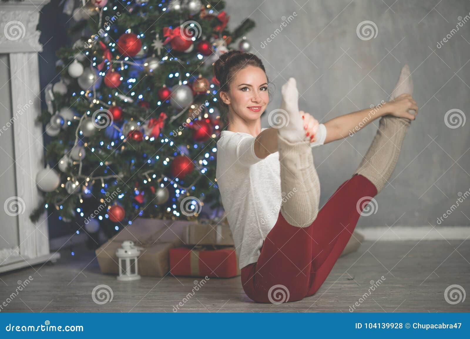 A jovem mulher consideravelmente flexível está fazendo esportes perto da árvore de Natal, esportes e conceito do feriado