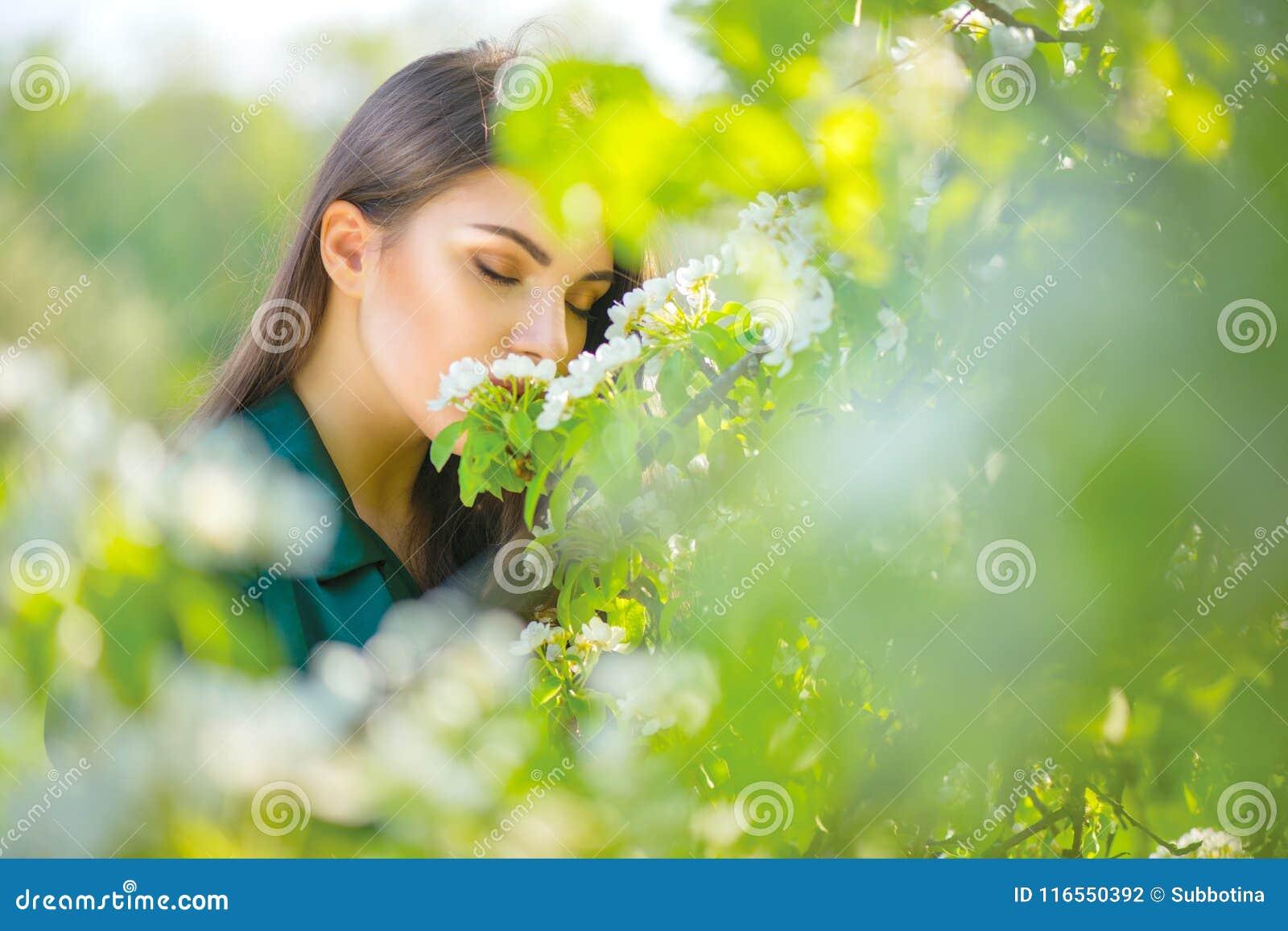 Jovem mulher da beleza que aprecia a natureza no pomar de maçã da mola, menina bonita feliz em um jardim com as árvores de fruto