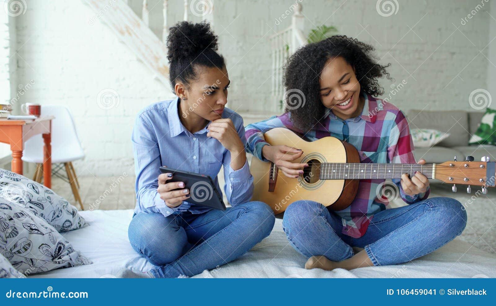 Jovem mulher da raça misturada com o tablet pc que senta-se na cama que ensina sua irmã adolescente jogar em casa a guitarra acús