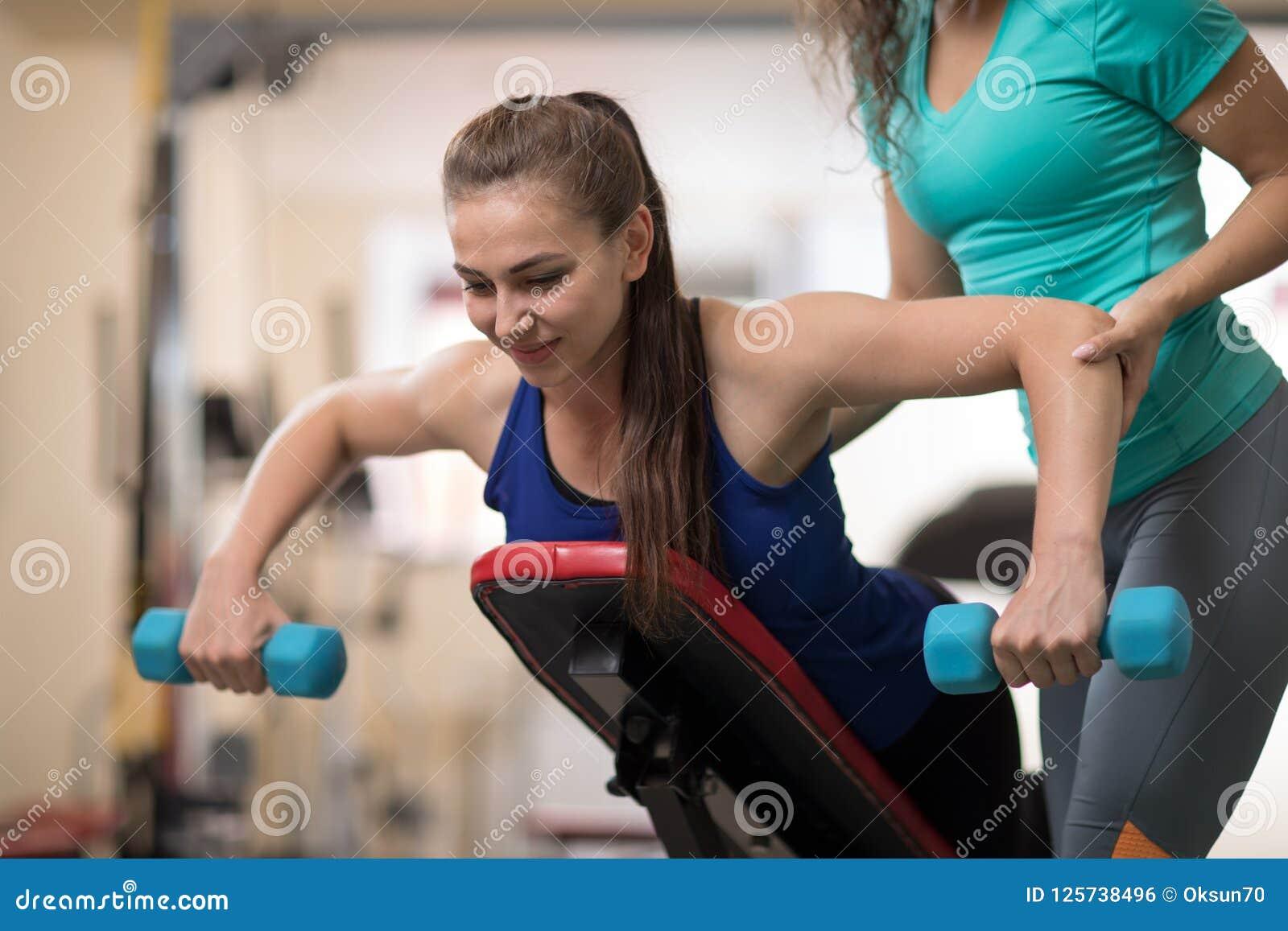 Jovem mulher de ajuda do instrutor pessoal com equipamento de treino do peso no gym