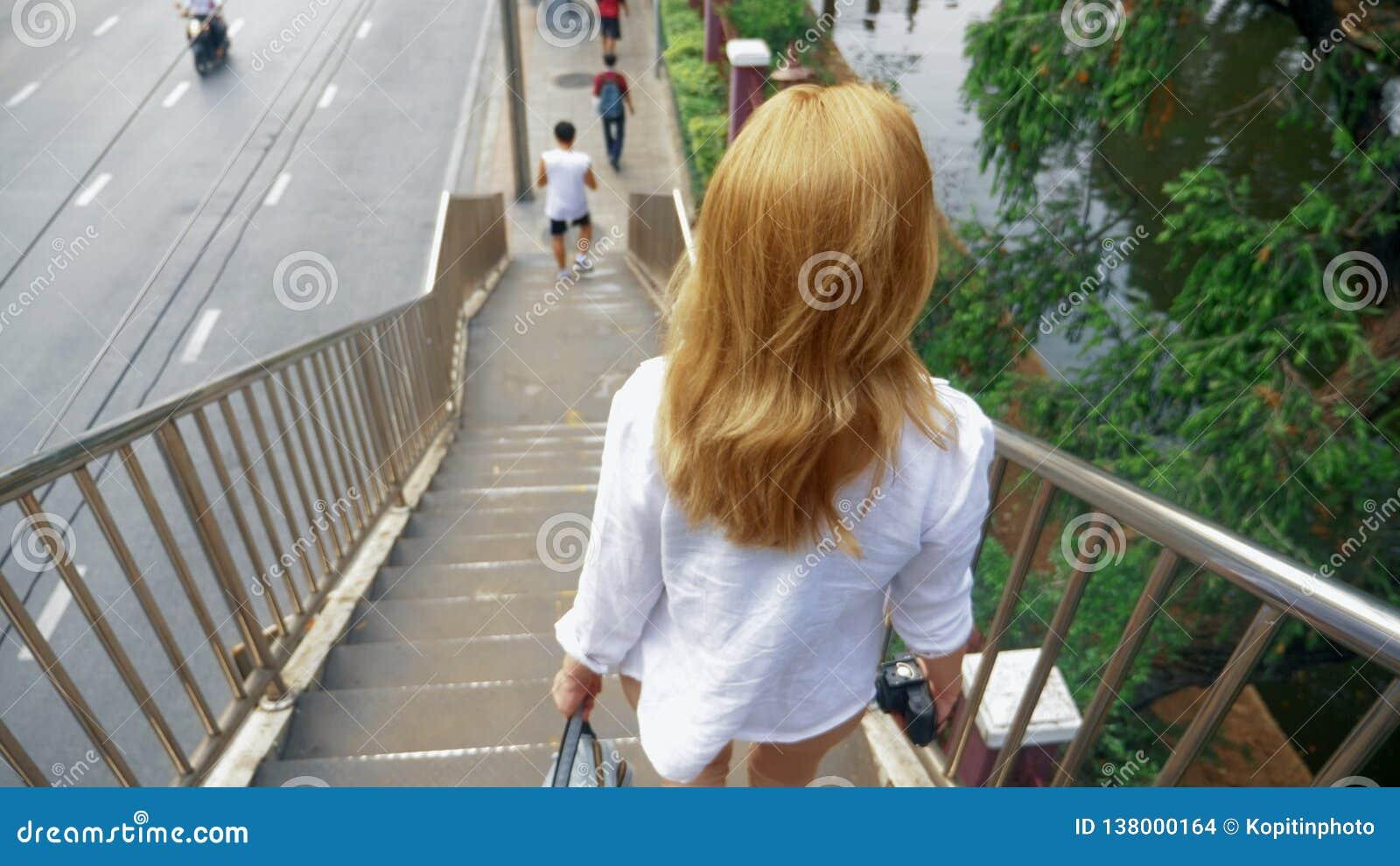 Jovem mulher de encantamento com o cabelo dourado, andando no centro da cidade, anda através da ponte