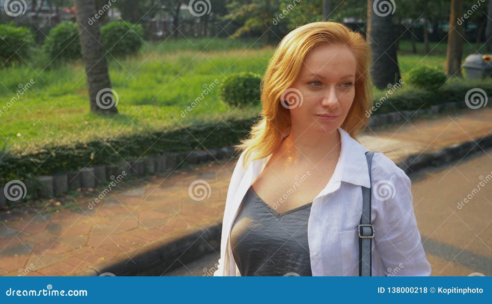 Jovem mulher de encantamento com o cabelo dourado que apressa-se no centro da cidade
