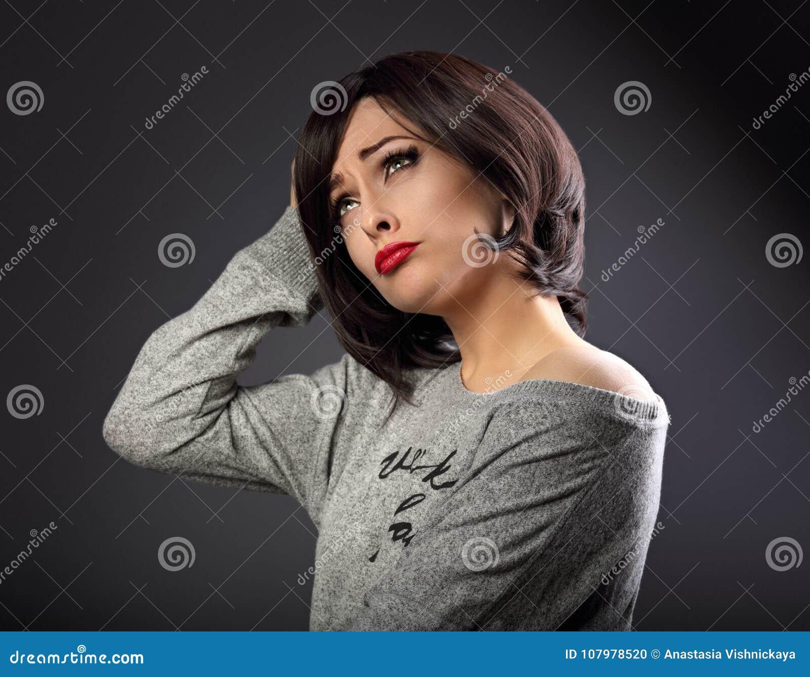 2fbb6d611 Jovem mulher de pensamento fazendo caretas infeliz cética com o penteado  preto curto que olha acima no fundo vazio do cinza do espaço da cópia