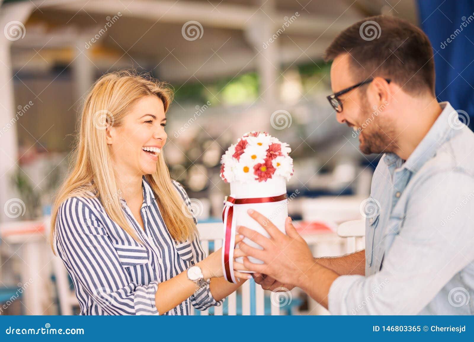 Jovem mulher de riso que recebe um presente das flores
