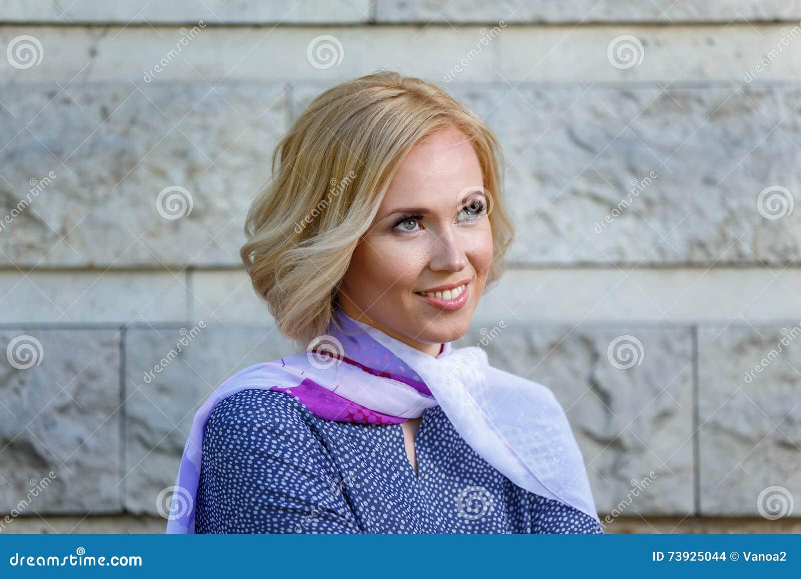 Jovem mulher de sorriso bonita perto da parede de pedra