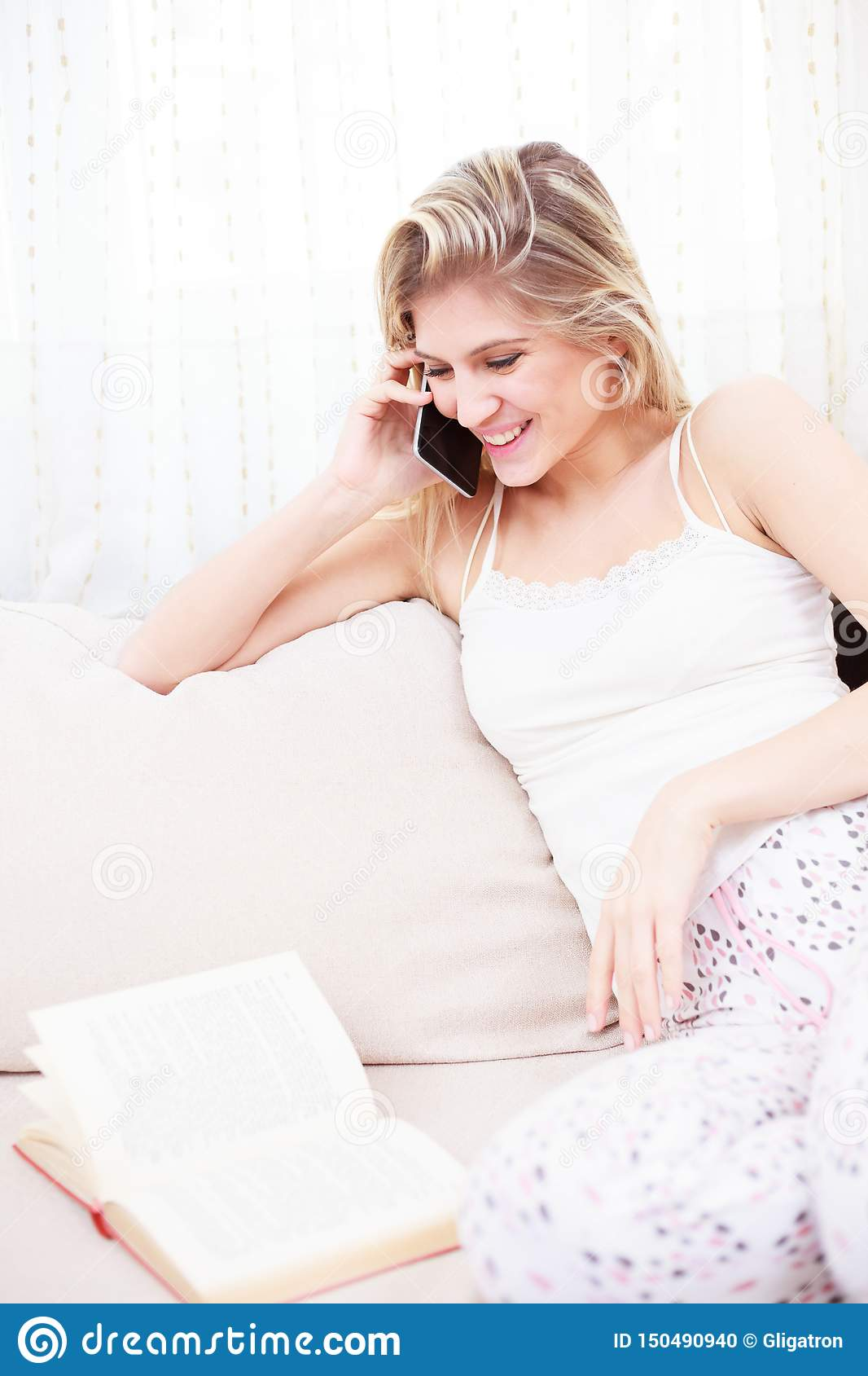 Jovem mulher de sorriso bonita que fala no telefone