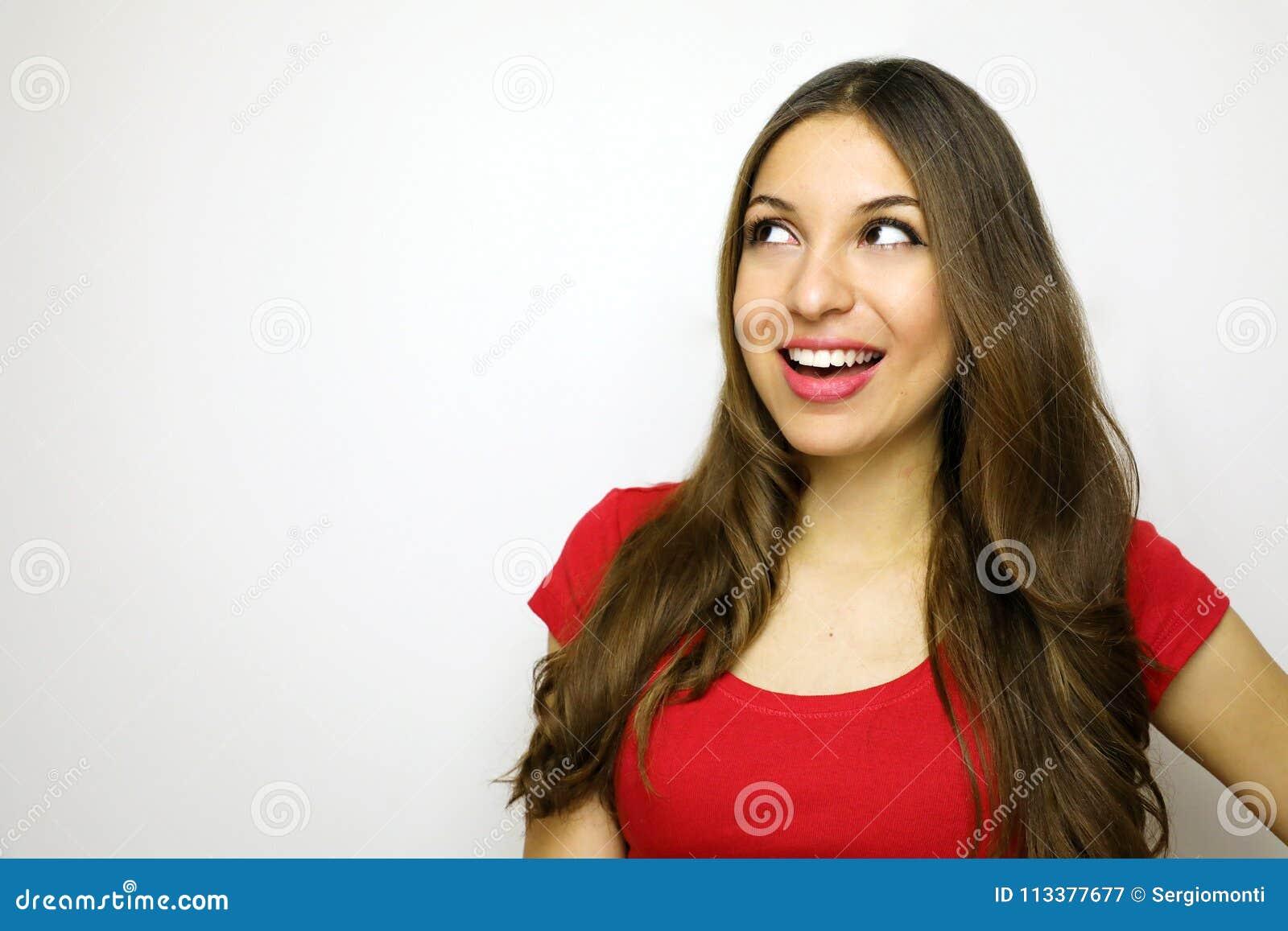 Jovem mulher de sorriso com o t-shirt vermelho que olha ao lado no fundo branco Copie o espaço