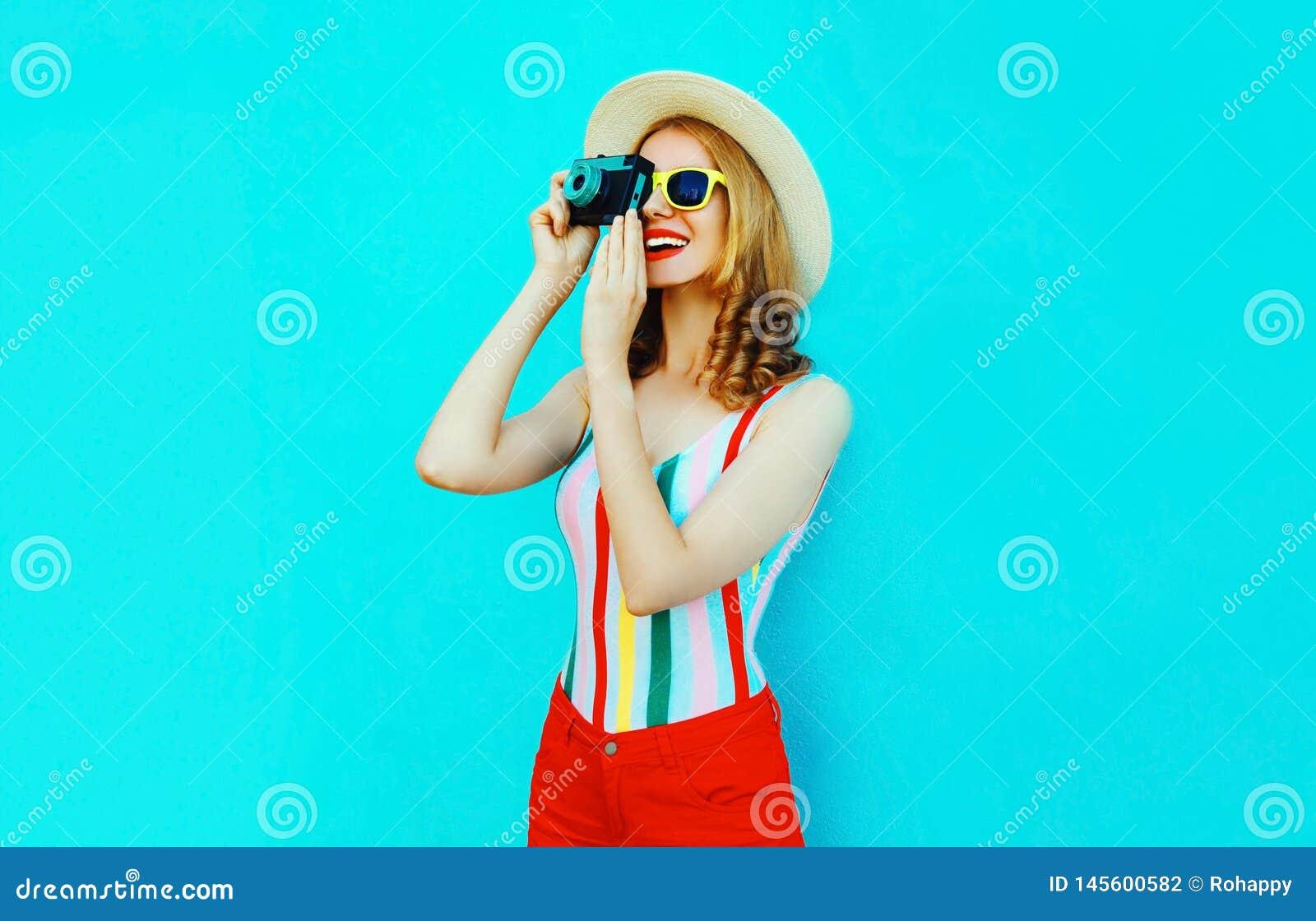 Jovem mulher de sorriso feliz colorida que guarda a câmera retro no chapéu de palha do verão que tem o divertimento na parede azu