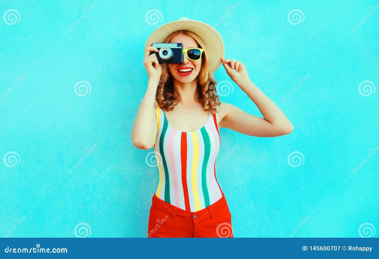 Jovem mulher de sorriso feliz colorida que guarda a c?mera retro no chap?u de palha do ver?o que tem o divertimento na parede azu