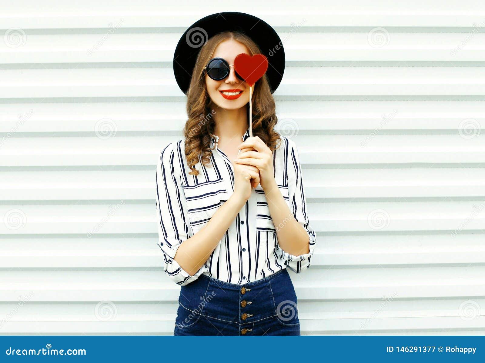 Jovem mulher de sorriso feliz do retrato que esconde seu olho com coração vermelho o pirulito dado forma no chapéu redondo preto,