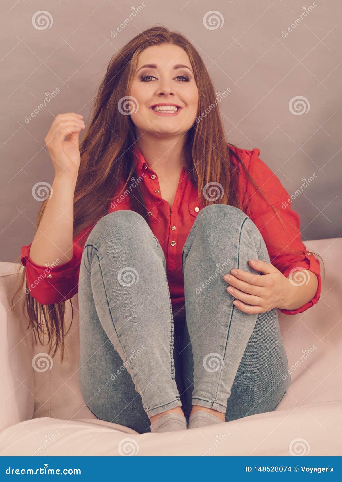 Jovem mulher de sorriso feliz no sofá