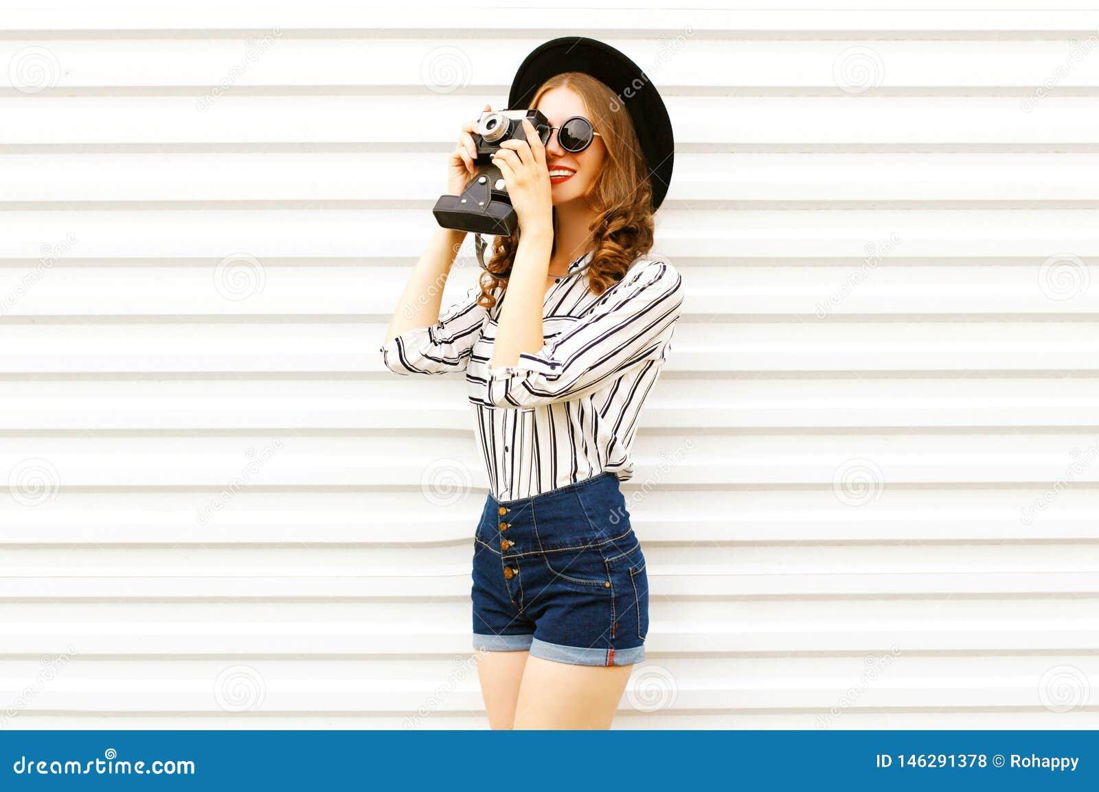 Jovem mulher de sorriso feliz que guarda a c?mera do filme do vintage no chap?u redondo preto, short, camisa listrada branca na p
