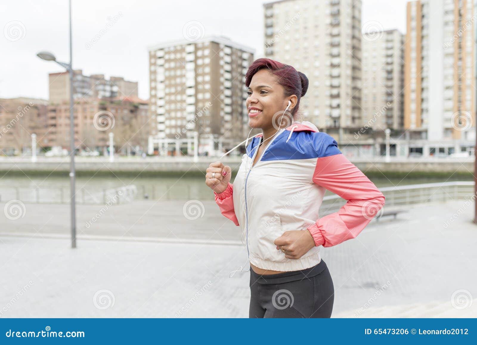 Jovem mulher de sorriso que corre na rua