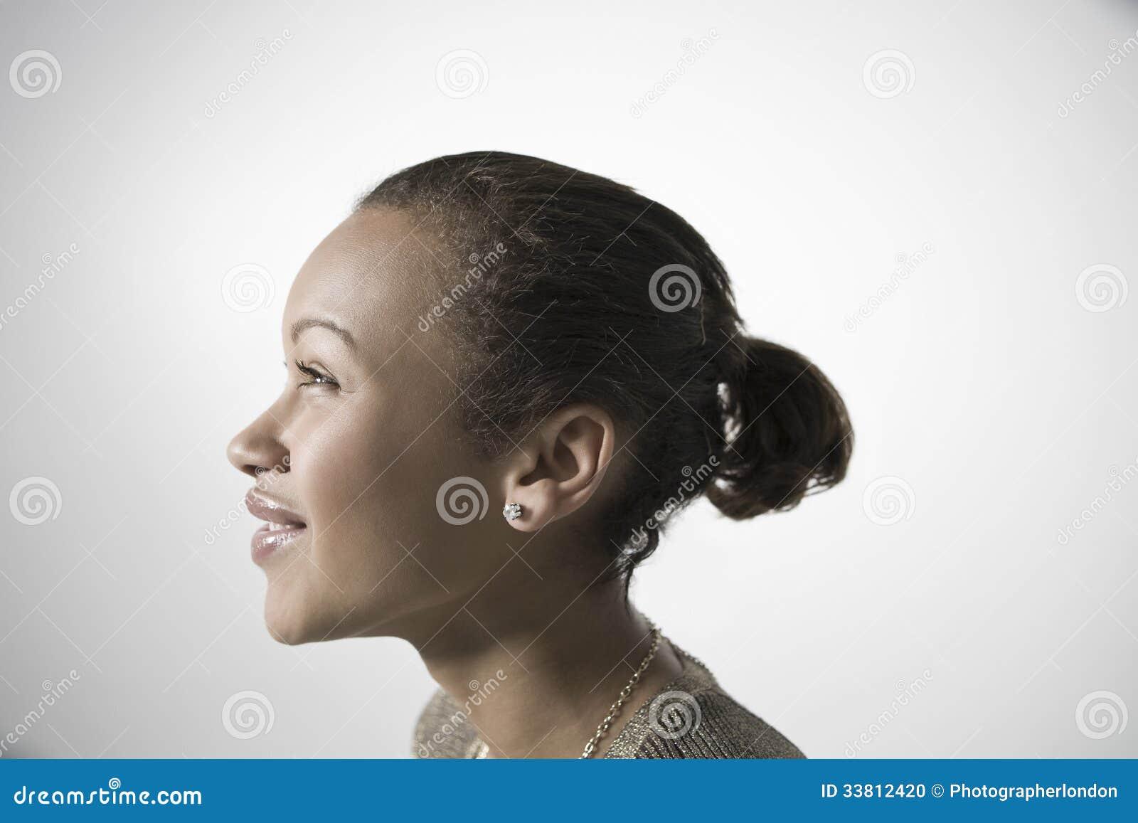 Jovem mulher de sorriso que olha ACIMA