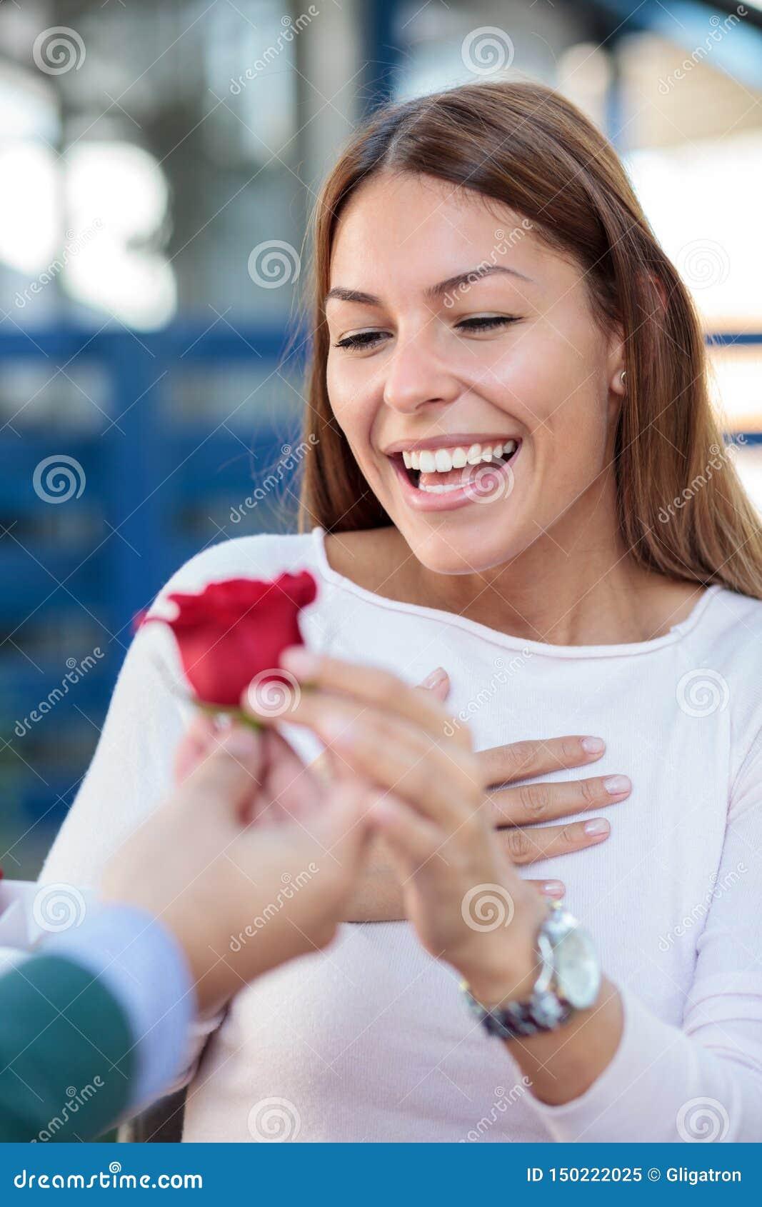 Jovem mulher de sorriso que recebe uma única rosa vermelha de seu noivo ou marido