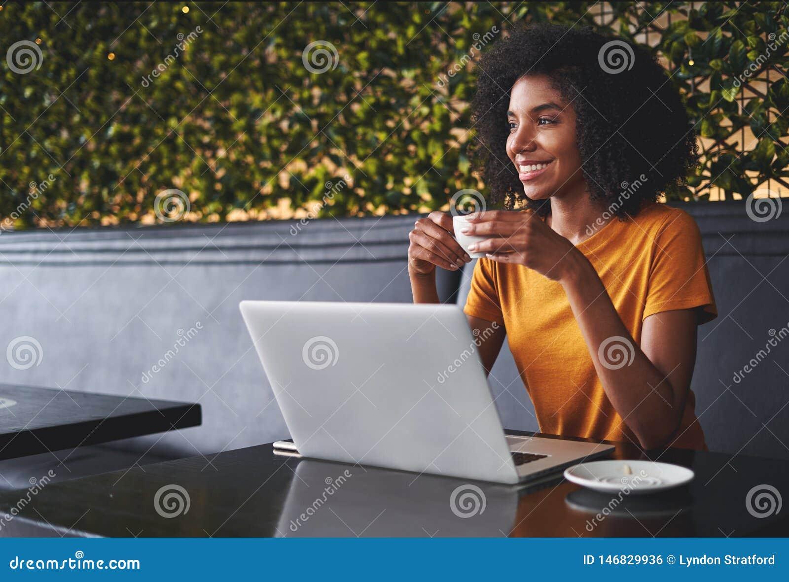 Jovem mulher de sorriso que senta-se no café que guarda o copo de café à disposição