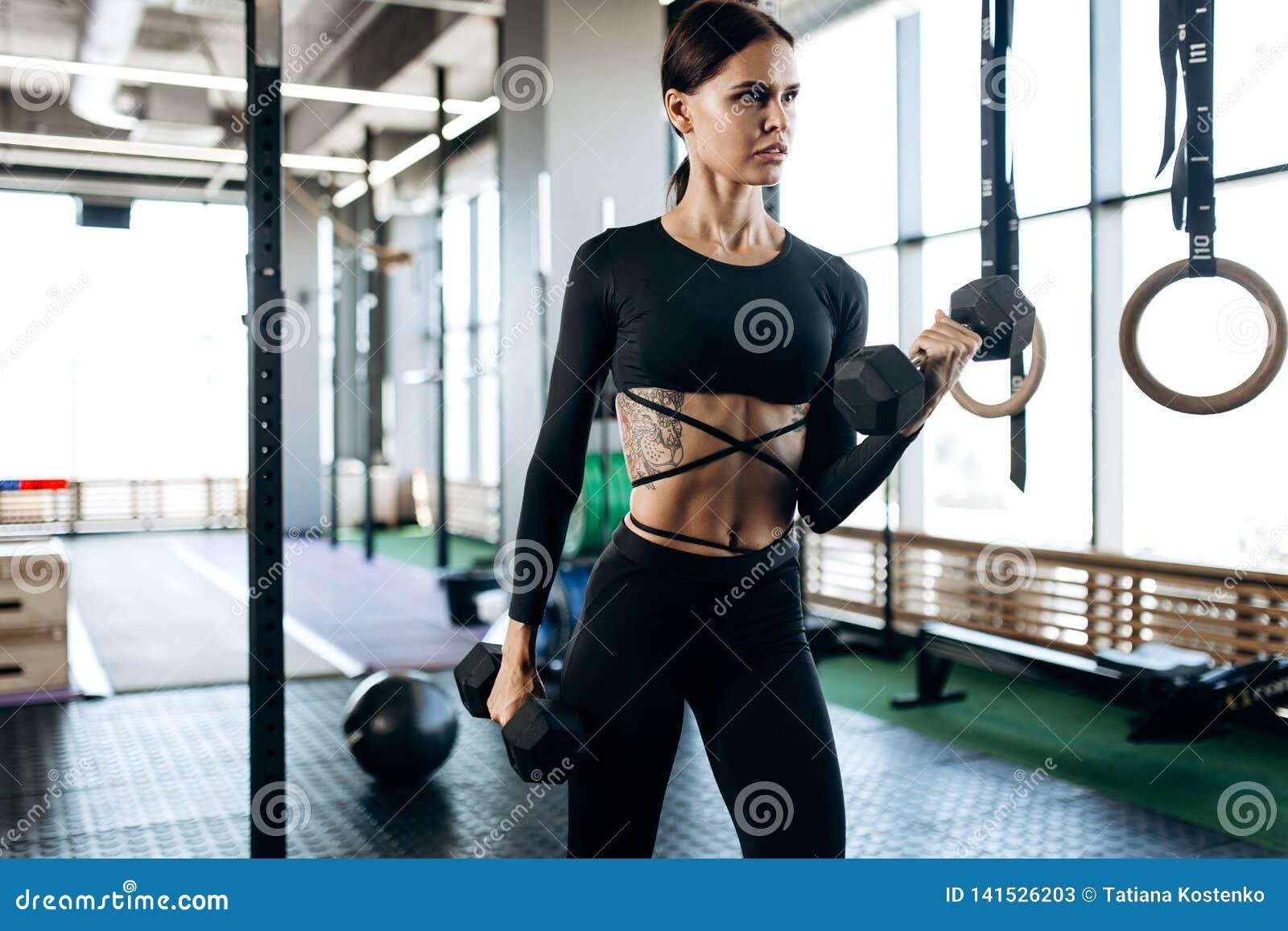 A jovem mulher delgada com a tatuagem vestida em um sportswear preto está fazendo exercícios com pesos no gym