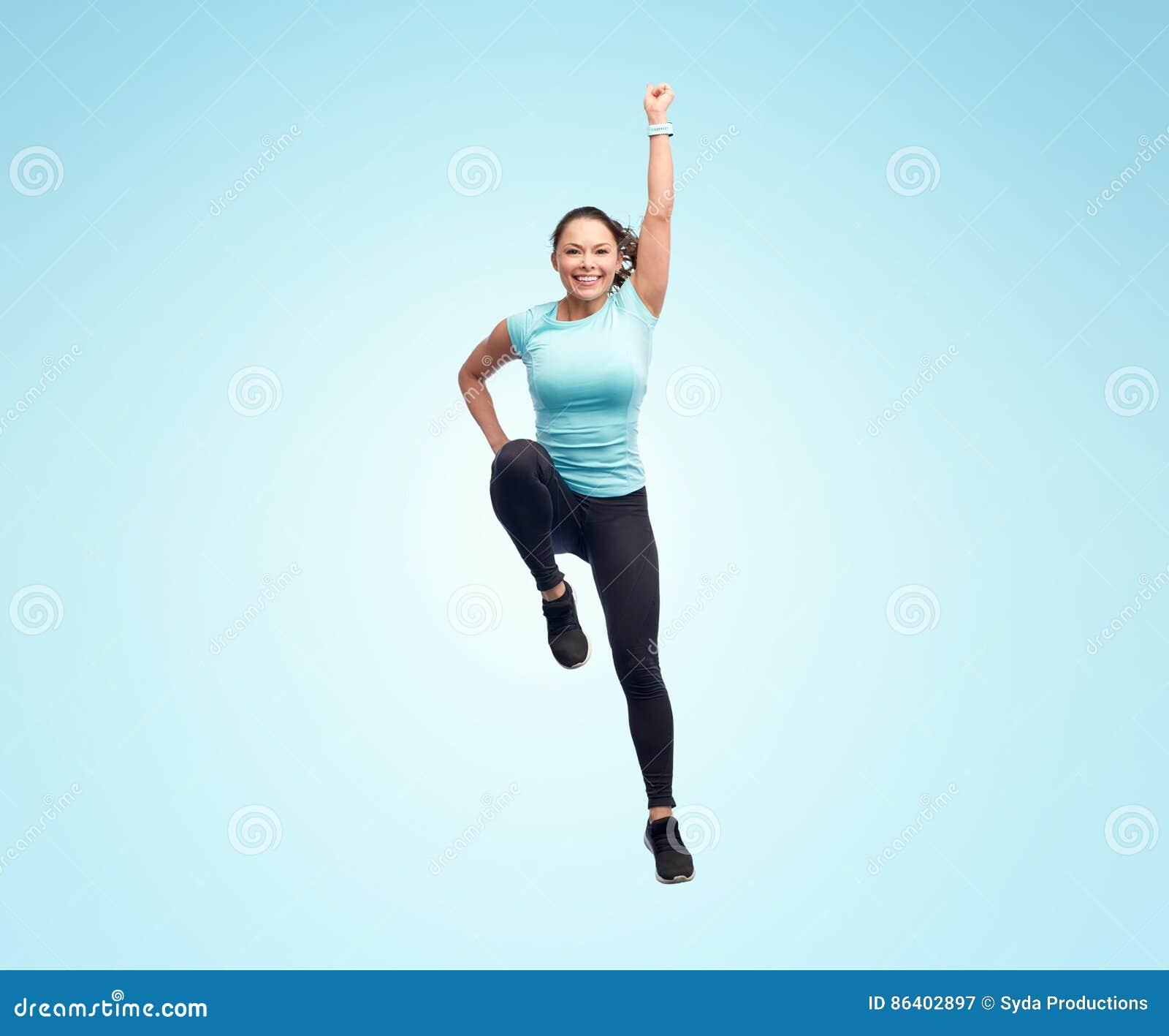 Jovem mulher desportiva de sorriso feliz que salta no ar