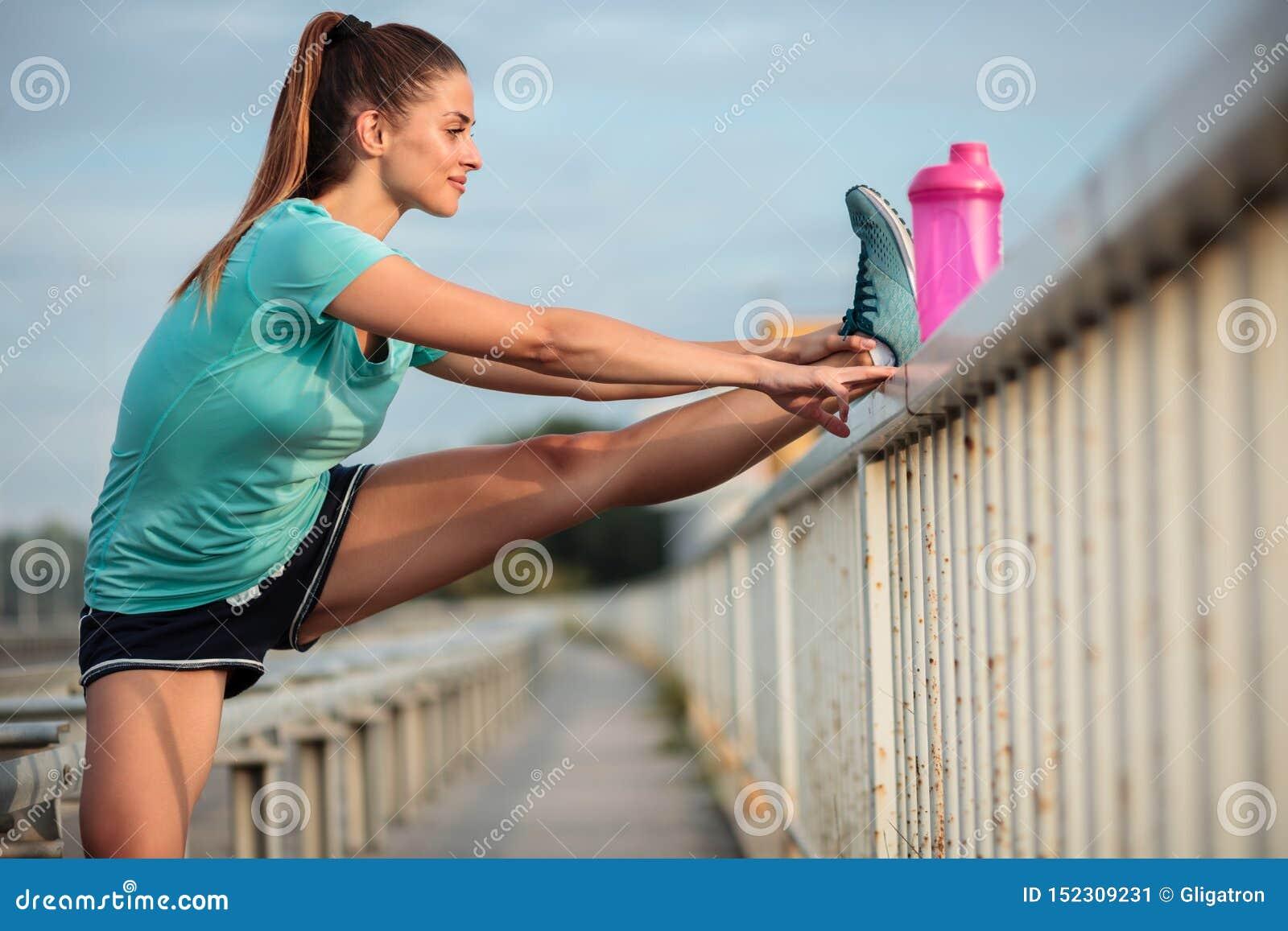 Jovem mulher determinada que estica os pés após um exercício urbano exterior duro