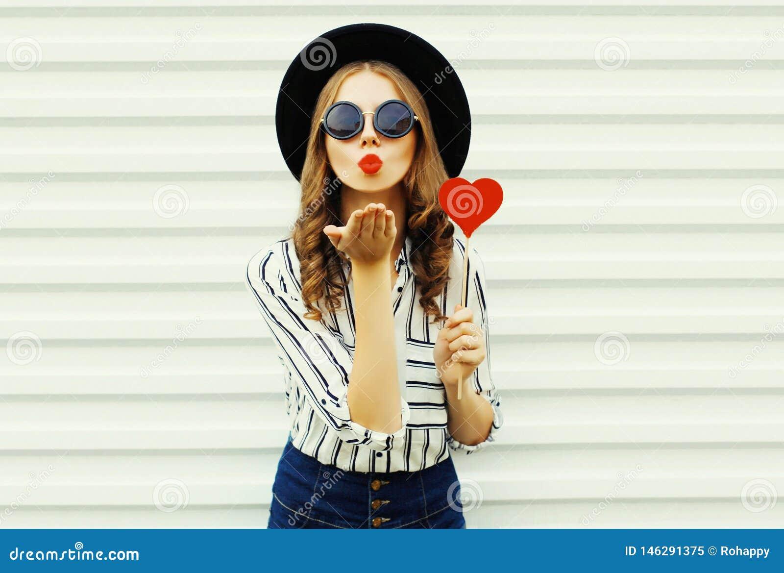 Jovem mulher do retrato que funde os bordos vermelhos que enviam o beijo doce do ar com coração vermelho o pirulito dado forma no