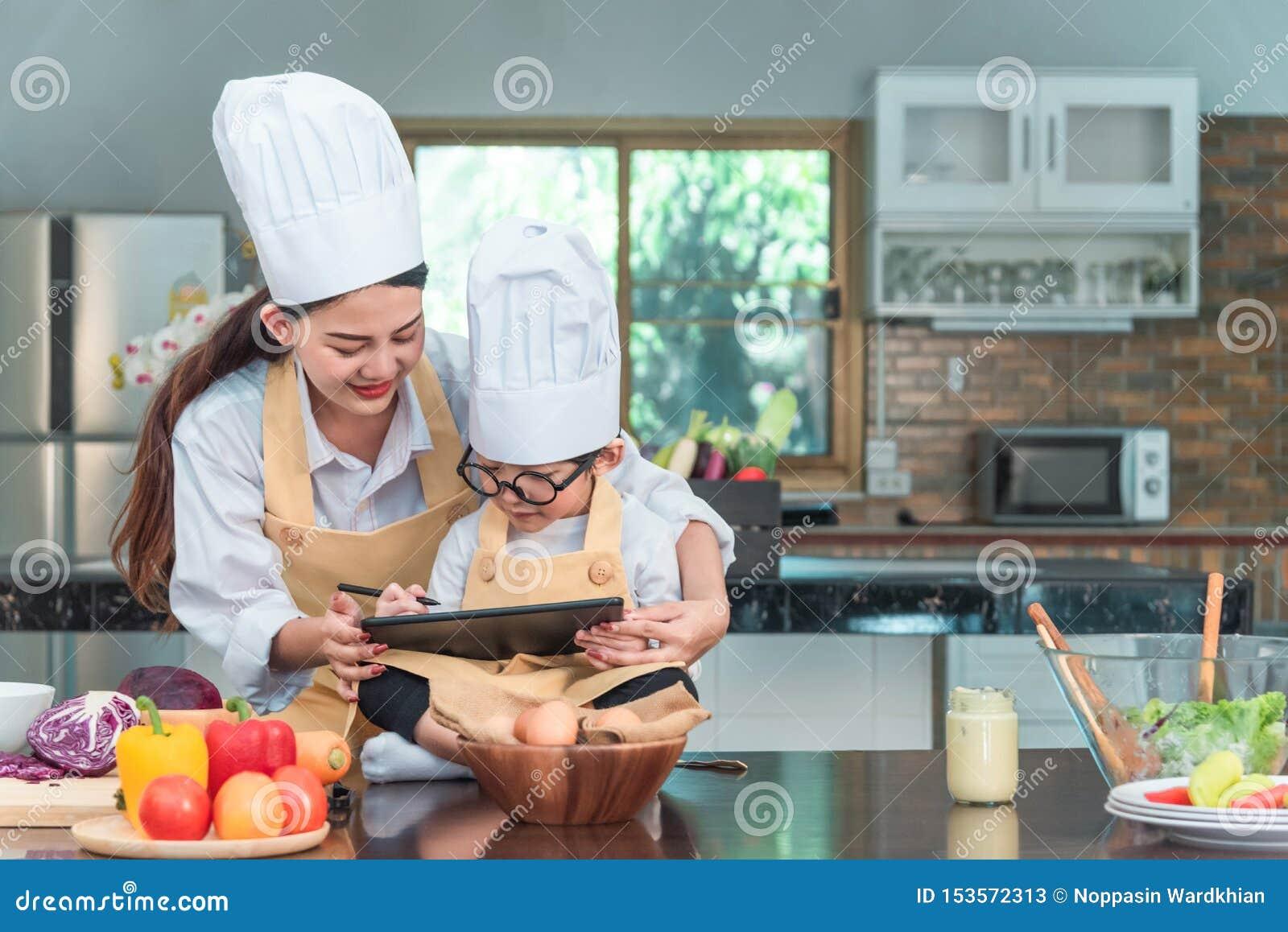 Jovem mulher e criança que usa o tablet pc ao cozinhar na cozinha Householding, alimento saboroso e tecnologia digital no estilo