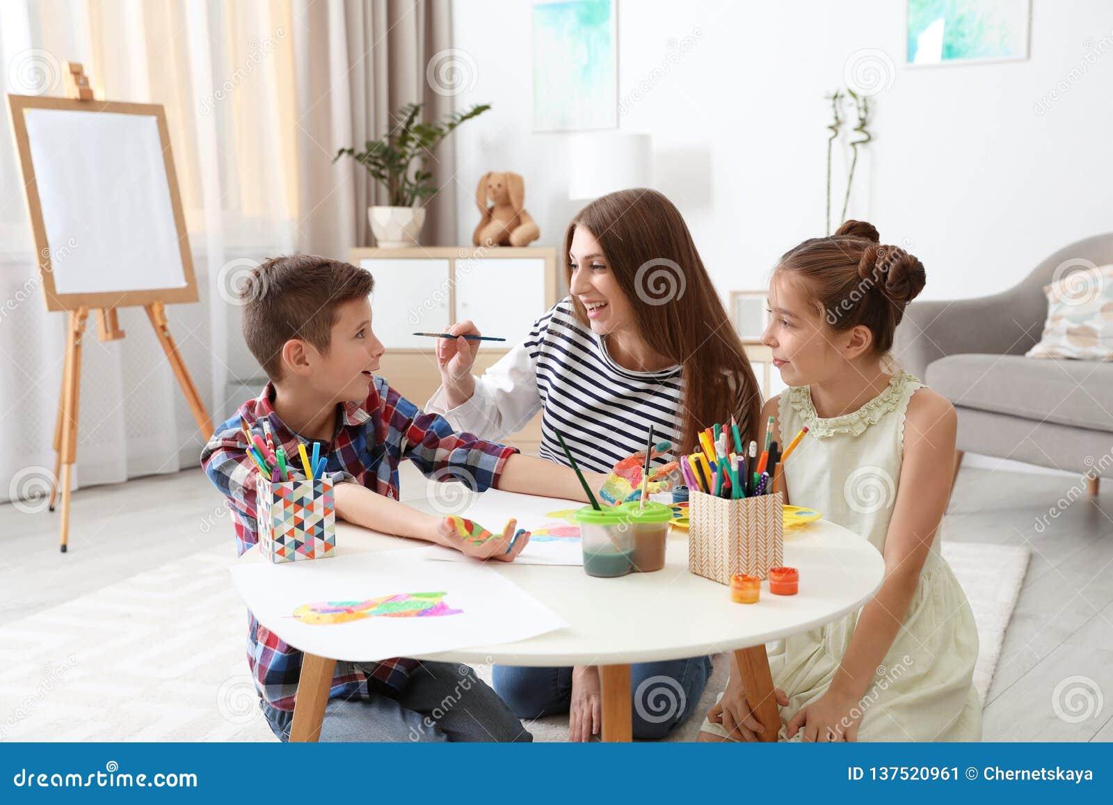Jovem mulher e crianças que têm o divertimento com pinturas