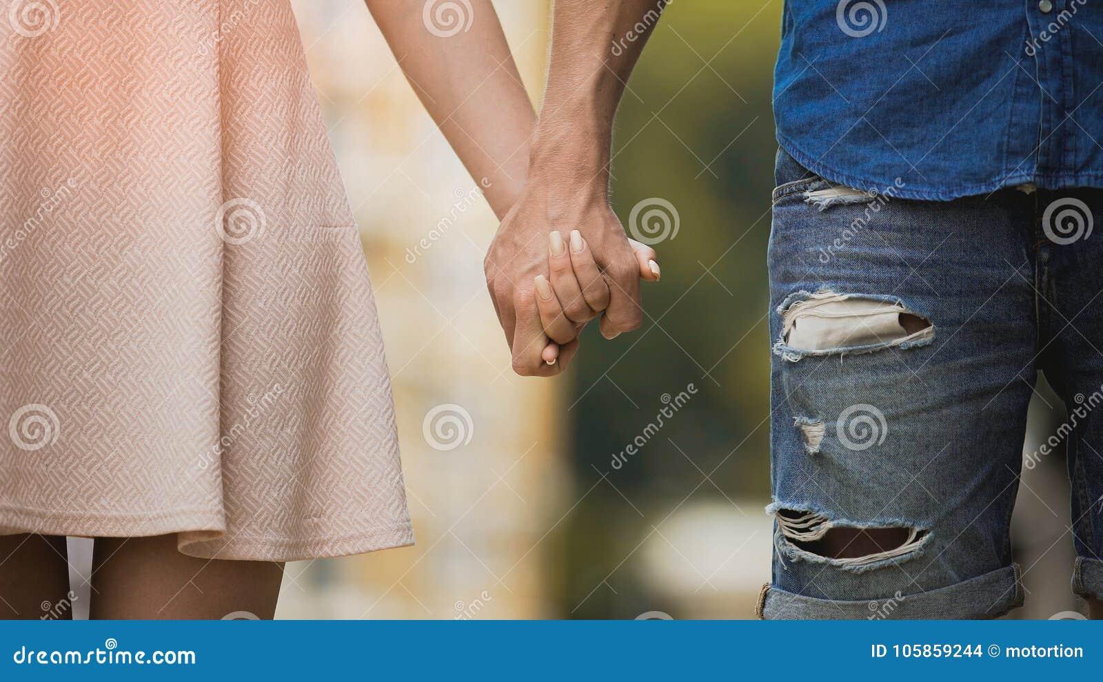 Jovem mulher e homem que guardam as mãos, relacionamento macio de pares doces, amor