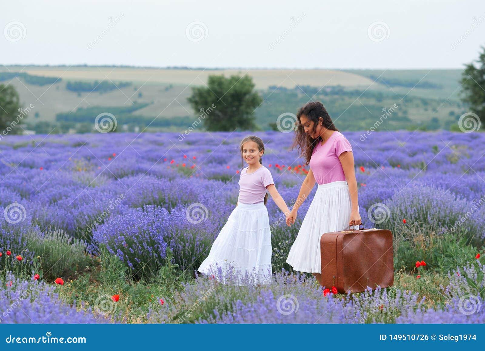 A jovem mulher e a menina est?o andando atrav?s do campo de flor da alfazema, paisagem bonita do ver?o