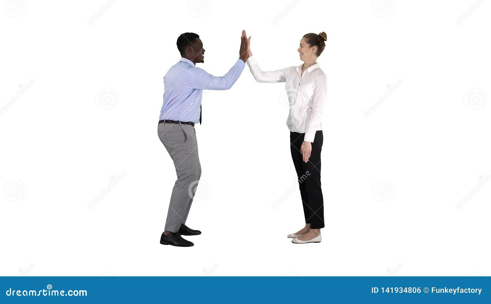 A jovem mulher e o homem novo na roupa formal dão altamente cinco no fundo branco