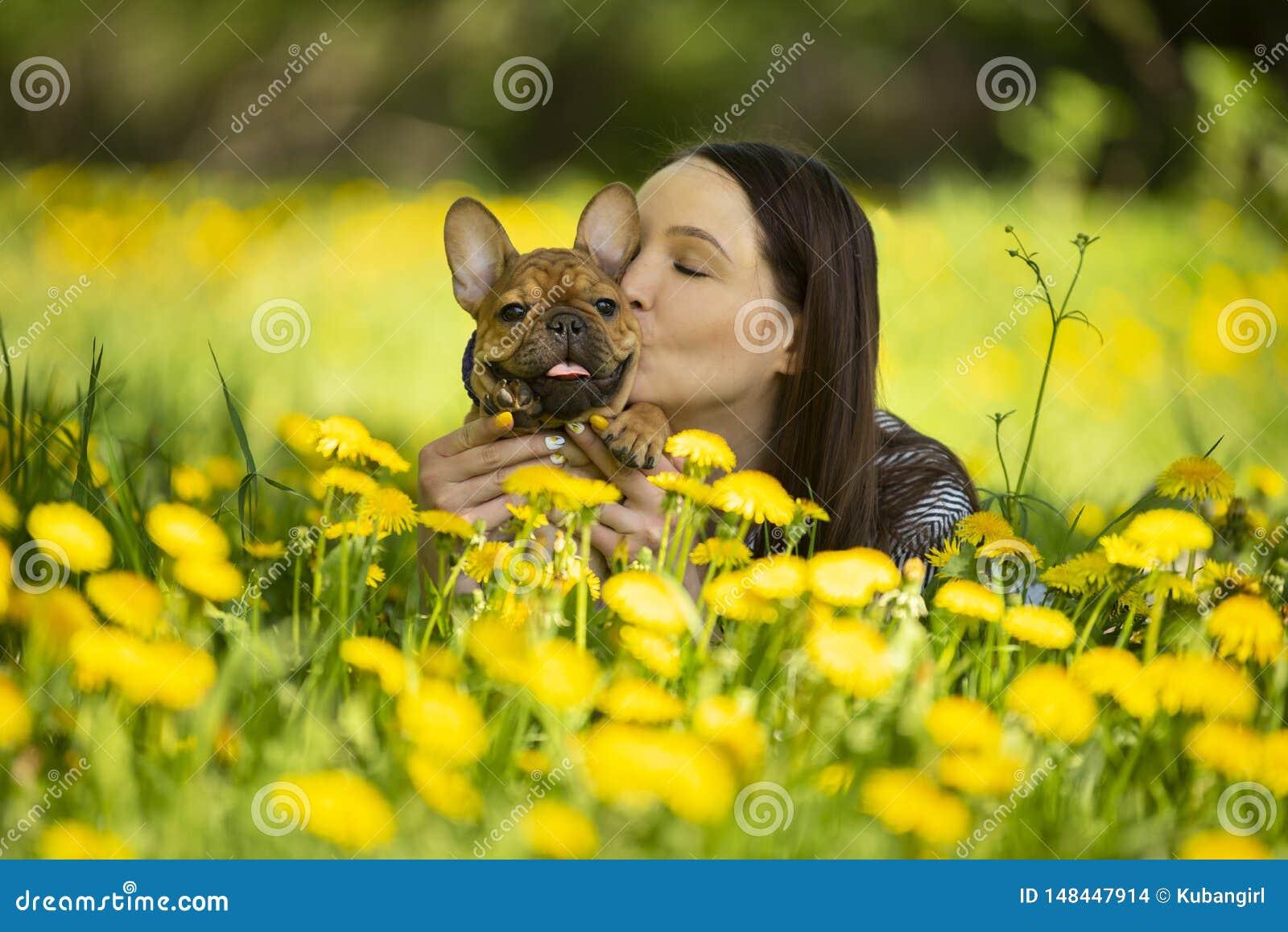 A jovem mulher e um cachorrinho do buldogue francês estão descansando em um parque
