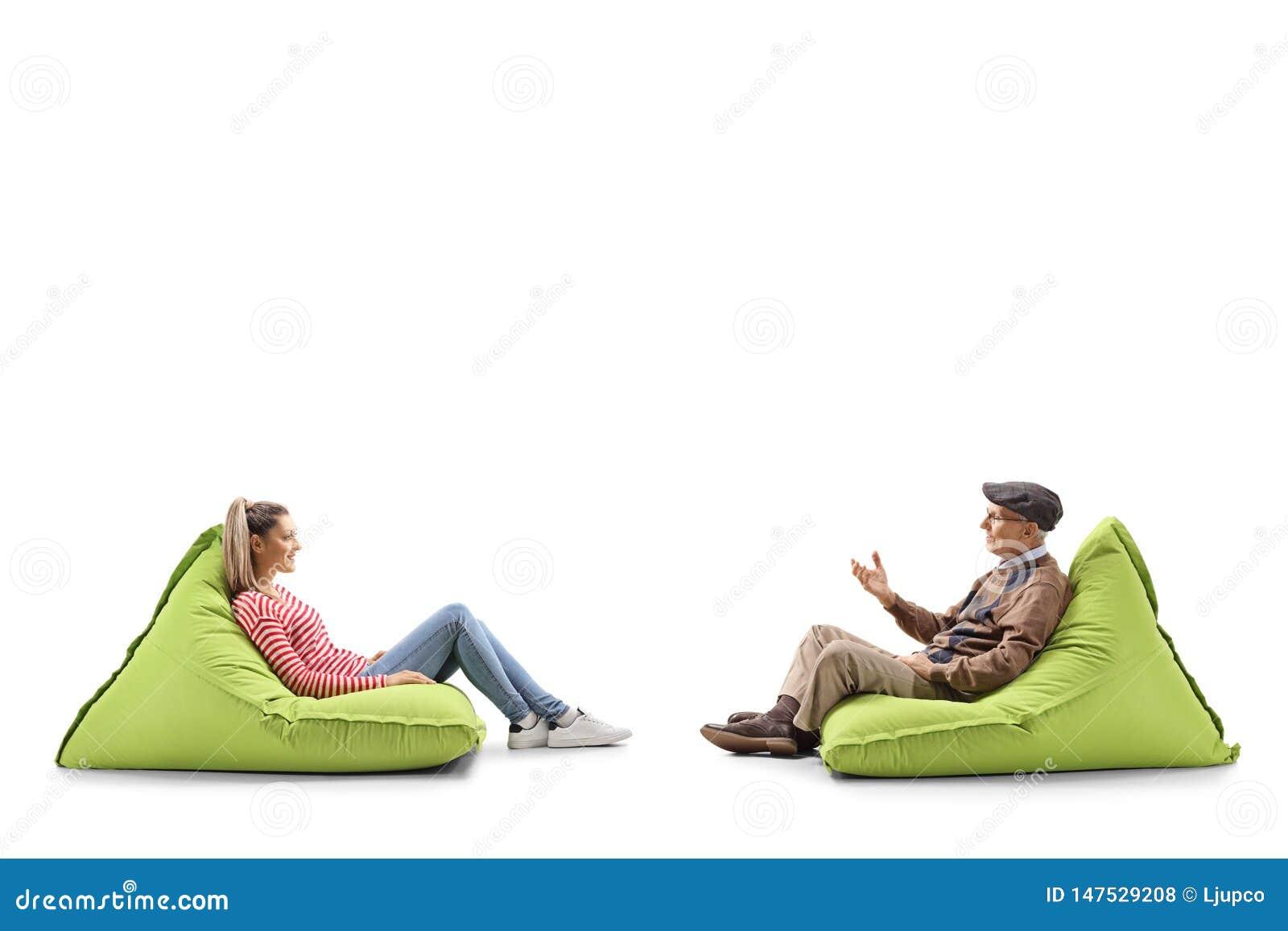 Jovem mulher e um homem superior que senta-se em sacos de feijão e que tem uma conversação